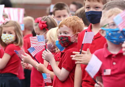 Butler Catholic kindergartener Brody Smith holds up a minuture flag with his clasmates during Butler Catholic's 9/11 ceremony Friday. Seb Foltz/Butler Eagle 09/10/21