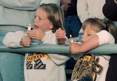 Emily Hamm, 7, and her sister Olivia, 4, both of knox, hold candles as part of a ceremony held before Friday's Moniteau-Keystone game to honor those killed in Tuesday's terrorist attacks. EAGLE FILE PHOTO