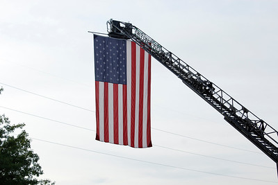 The Cranberry Township Volunteer Fire Department hung a flag from a ladder truck as part of memorial ceremonies in honor of the victims of 9/11. Julia Maruca/Butler Eagle