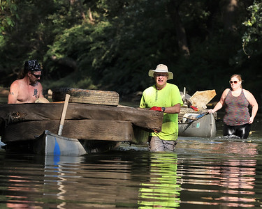 Adam Speer (left), Chris Arnold and Amanda Love bring a load of trash down Connoquenessing creek during Saturday's cleanup. Seb Foltz/Butler Eagle 09/11/21