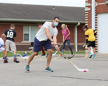 Pittsburgh Penguins defender Brian Dumoulin passes a puck to a Knoch Middle School student during a visit to the school Thursday. The visit was part of an academic achievement reward for students in the elementary and middle School. Seb Foltz/Butler Eagle 09/16/21