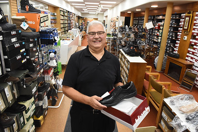 Jimmy Chiprean of Miller's Shoes shows off a new pair of shoes. The store has been closed since January after sustaining damage from fire in an adjacent building. Harold Aughton/Butler Eagle