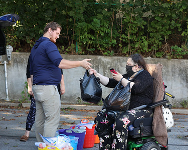 Nick Leturgey hands a bag of produce to Butler area resident Bridget G. during Friday's Community Partnership food distribution. Seb Foltz/Butler Eagle 09/24/21