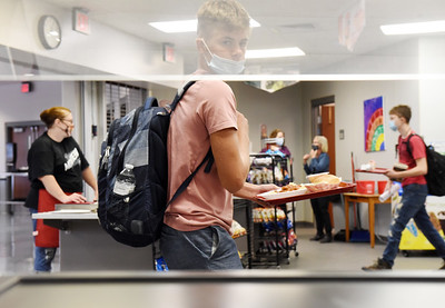 Ashton Grossman, a 9th grader at Moniteau High School, walks past a warming tray that is generally filled with pizza but because of shortages in the supply chain the district is running low on some food and general supplies.  Harold Aughton/Butler Eagle