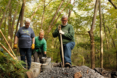 Volunteers Chuck Davies, Nicole Hacke and Mary Emmett haul gravel during the National Public Lands Day volunteer cleanup at Jennings Environmental Education Center on Saturday. Julia Maruca/Butler Eagle