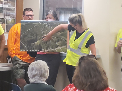 Laura Mason demonstrates how construction of the sewer system could impact the forest areas of Connoquenessing Township, using photo prints she took with a drone. EDDIE TRIZZINO/BUTLER EAGLE