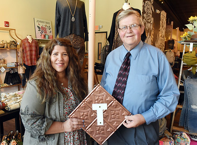 Angela Dawson, owner of Local Boutique 16063, and Randall Hart, former council member hold a placard of tin to be put on display. According to Hart, a number of businesses still have old tin roofs inside their business that were installed in the late 1800s.  Harold Aughton/Butler Eagle