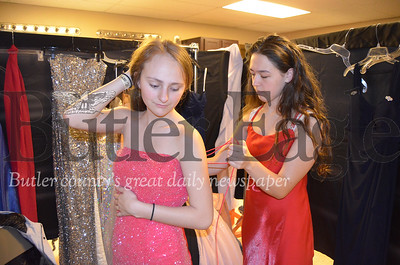 """Photo by Alexandria Mansfield. North Catholic High School Senior Emily Gregor (right) helps her friend and fellow senior Greta Bender (left) into a dress at the Cranberry Community United Presbyterian Church's annual """"I Found the Gown"""" sale on Saturday."""