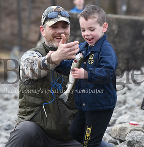 """Five-year-old, Jack Raybuck of Mars gets a little help with his first fish from his father, Curtis, Saturday, April 6, during the Mentored Youth Trout Day at Glad Run Lake.  See extended cutline below: With the Sun tucked behind the clouds, Curtis Raybuck of Mars trekked across the shore line of Glade Run Lake with his three children, Owen, 7; Jack, 5; and 18-month-old Ava in tow. The family had been up since 4:30 a.m. in preparation of the first day of the Mentored Youth Trout Day. They made their way to the breast of the dam near the spillway.  Curtis baited the poles while Ava sat patiently in a little red wagon as the boys frolicked nearby. He checked the time on his cell phone: """"8:09"""" he exclaimed and positioned Owen and Jack along the shore line. Helping his sons cast their lines into the lake, he encouraged them to be patient and watch their bobbers carefully. Both Owen and Jack had fish on their line but failed to bring them a shore. However, on his second attempt, Jack found success, catching his first rainbow trout.  """"This is the best day for youth fishing,"""" said Curtis Raybuck. """"It's not as fun with the adult anglers... this is perfect!"""""""