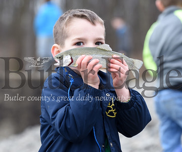 """Harold Aughton/Butler Eagle: Five-year-old, Jack Raybuck of Mars proudly displays his first fish he caught at Glade Run Lake, Saturday, April 6, during the Mentored Youth Trout Day at Glad Run Lake.  See extended cutline below With the Sun tucked behind the clouds, Curtis Raybuck of Mars trekked across the shore line of Glade Run Lake with his three children, Owen, 7; Jack, 5; and 18-month-old Ava in tow. The family had been up since 4:30 a.m. in preparation of the first day of the Mentored Youth Trout Day. They made their way to the breast of the dam near the spillway.  Curtis baited the poles while Ava sat patiently in a little red wagon as the boys frolicked nearby. He checked the time on his cell phone: """"8:09"""" he exclaimed and positioned Owen and Jack along the shore line. Helping his sons cast their lines into the lake, he encouraged them to be patient and watch their bobbers carefully. Both Owen and Jack had fish on their line but failed to bring them a shore. However, on his second attempt, Jack found success, catching his first rainbow trout.  """"This is the best day for youth fishing,"""" said Curtis Raybuck. """"It's not as fun with the adult anglers... this is perfect!"""""""