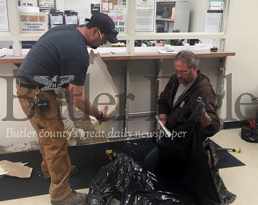 Butler County workers Ben Fallecker, left, and Jerry Barnhart remove old panels from the front counter at the office of District Judge William Fullerton in Butler. The office is being fitted with ballistic panels as part of the county's move to strengthen security at the seven district judge offices. The installation of the panels are being funded by a  state grant.