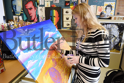 Harold Aughton/Butler Eagle: Butler senior Grace Clendenning works on a wall painting of a farmer's field.