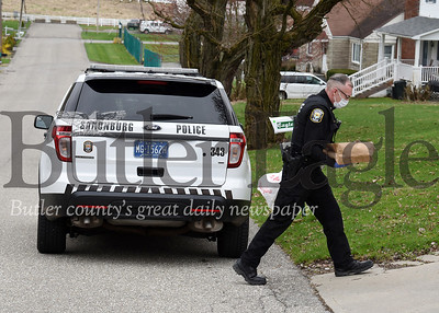 Harold Aughton/Butler Eagle: Saxonburg police chief Joe Beachem delivers a meal to a home on E. Main St. Tuesday afternoon, March 31, 2020.