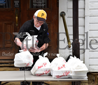 Harold Aughton/Butler Eagle: Hotel Saxonburg chef Alan Green places takeout meals to go for delivery by the Saxonburg police department Tuesday afternoon, March 31, 2020.