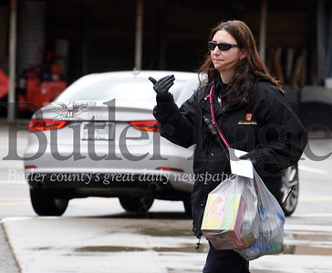 Harold Aughton/Butler Eagle: Amy Behun, fire department administrative assistant, directs traffic as she collects groceries and other items from volunteers as part of the fire department's outreach efforts to help those affected by the coronavirus.