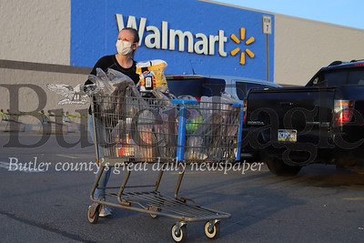 A masked shopper looks for her car in the Butler Walmart's parking lot Saturday evening. 04/04/20 Walmart recently began limiting shoppers, shortening store hours and having shoppers line up outside with appropriate social distance spacing when the store reaches capacity. Seb Foltz/Butler Eagle