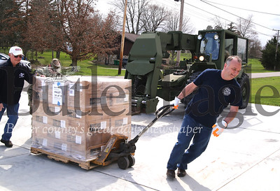 Chuck Glagola(right) and other volunteers assist the Army National Guard in unloading emergency meals at the Mercer Road Volunteer Fire Department Thursday. The guard delivered two truckloads totaling over 20,000 meals that will be distributed to area seniors in need. Seb Foltz/Butler Eagle
