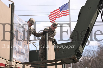 Army National Guard specialists Izekial Saleh(left) and Alex Belew help guide forklift opperations unloading emergency food supplies at the Middleton Fire Department Thursday. Guard members delivered over 20,000 meals to be distrubuted to area seniors through the Butler County Area Agency on Aging. Seb Foltz/Butler Eagle