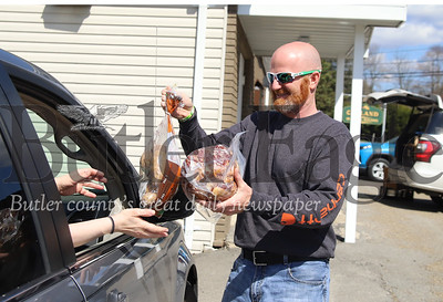Shawn Krill of Krill Recycling delivers a ham and a bag of potatos to a car in the Oakland Township municipal building parking lot Saturday 04/11/20. Krill partnered with longtime friend Zac Slater of Slater's Meats & More to distribute around 80 hams to area residents in need over the weekend. The hams were overstock from Slater's. Slater and Krill decided to cover the cost of the meet in an effort to help the community. Seb Foltz/Butler Eagle
