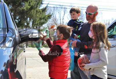 Mason Kril, 7, and his sister Madalyn, 9, deliver a bag of potatoes and half of a ham to a car in the Oakland Township municipal building parking lot while their father Shaun Krill of Krill Recycling and brother Mox, 3, look on. Krill and longtime friend Zac Slater of Slater's Meats & More in Karns City partnered to distribute around 80 half hams to area residents in need during the COVID-19 outbreak. Seb Foltz/Butler Eagle
