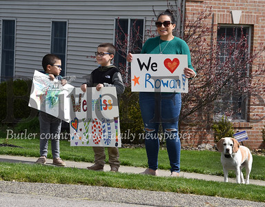 Harold Aughton/Butler Eagle: Hunter, 4, Nate, 7, and Sandra Zugell along with their pet beagle, Wrigley, showed their support to the teachers and first responders that drove past their home Monday morning, April 27, 2020.