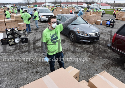 Harold Aughton/Butler Eagle: Zach Gillispie, sophomore at Grove City College, gives the go ahead to move the cars forward during the Greater Pittsburgh Area Food Bank food distribution event held at the Big Butler Fairgrounds, Tuesday, April 28, 2020.