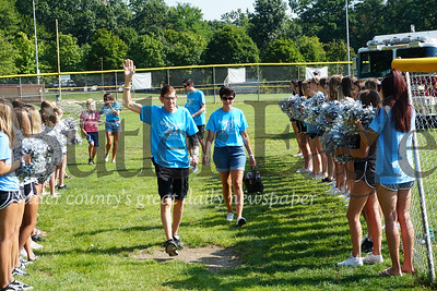 Photo by J.W. Johnson Jr. Dave Pritchard, left, and his wife, Julie, make their way through a tunnel of Seneca Valley cheerleaders Saturday during opening ceremonies of the Cranberry Community Uniting People softball tournament in Community Park.