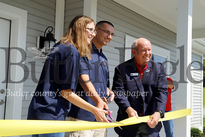 U.S. veteran Justin Hendrickson and his wife Jennie cut the ceremonial ribbon celebrating their new home with  retired brigadier general and Homes for Troups president/CEO Tom Landwermeyer Saturday 08/03/12. Hendrickson lost a leg serving in Iraq and his wife is a brain cancer survivor. Seb Foltz/Butler Eagle