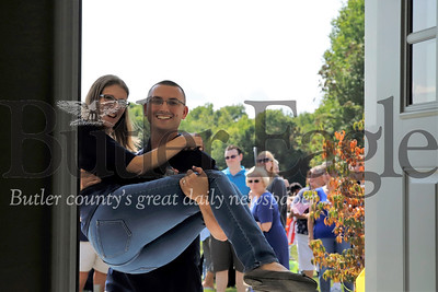 U.S. veteran Justin Hendrickson carries his wife Jennie across the threshold of their new home Saturday 08/03/12. Hendrickson, who lost a leg serving in Iraq, and his wife,  a brain cancer survivor, recieved the home through Homes for Troups. Seb Foltz/Butler Eagle