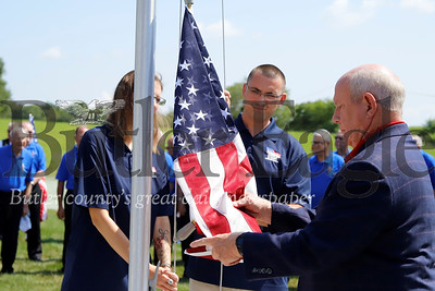 U.S. veteran Justin Hendrickson(center) and his wife Jennie raise the American flag with  retired brigadier general and Homes for Troups president/CEO Tom Landwermeyer Saturday at their new house 08/03/12. Hendrickson lost a leg serving in Iraq and his wife is a brain cancer survivor. Seb Foltz/Butler Eagle