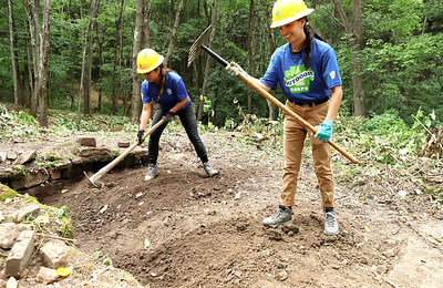 Student Conservation Association crew members, Breanna DeCaro(right), 22, and Emily Abreu, 23, dig around an old foundation clearing invasive Japanese knotweed on the Hilltop Trail at Moraine State Park Wednesday. Aug.26. Park officials said they are looking at options for further excavating and researching the old structure. Seb Foltz/Butler Eagle