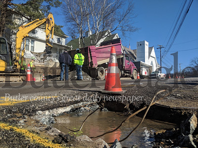 The Evans City Sewer and Water Authority discovered the breaks on Main Street, pictured here, and Elizabeth Avenue on Sunday and have been working to patch them throughout the day, issuing a boil advisory Monday morning after a possible drop in water pressure raised contamination concerns. pictures by Caleb Harshberger