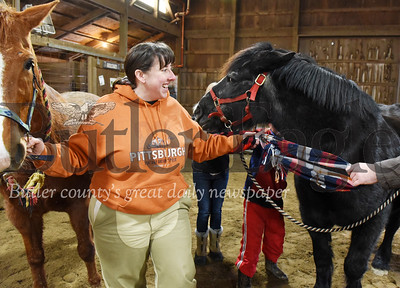 Harold Aughton/Butler Eagle: Cheri Herschell of Zelienople, a volunteer for the Glade Run Adventures, participates into an activity connecting the group by scares while holding onto Hersey, left, a quarter horse/thoroughbred mix and Pumpkin, a 26-year-old Percheron.