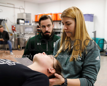 Slippery Rock University student trainer Matt Zittle (left) consults with school athletic trainer Jael Funte while she treats sophomore track athlete Cecily Greggs. Seb Foltz/Butler Eagle
