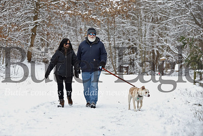 Mary and Mike Pavilonis and their dog Rolo enjoy a snowy walk during Moraine State Park's Winterfest Saturday. Seb Foltz/Butler Eagle 02/08/20