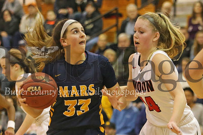 Mars' Bella Pelaia drives to the hoop against Moon's Emma Theodorsson (#14) in Tuesday night's playoff game at North Hills. Seb Foltz/Butler Eagle