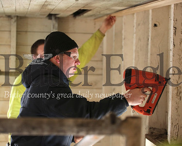 Mike Ferringer tests a nail gun before nailing in the first piece of the new ceiling in the old Foltz School House on Route 8 south of Slippery Rock. Volunteers from the Eastern Atlantic States Council of Carpenters will be spending the next few weekends helping restore the historic building. Seb Foltz/Butler Eagle 02/15/20