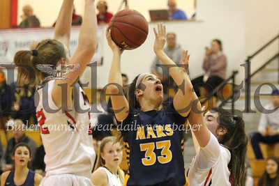 Mars' Bella Pelaia drives to the hoop against Moon'sReilly Sunday (#22 left) and Brianna Toal (#21) in Tuesday night's playoff game at North Hills. Seb Foltz/Butler Eagle