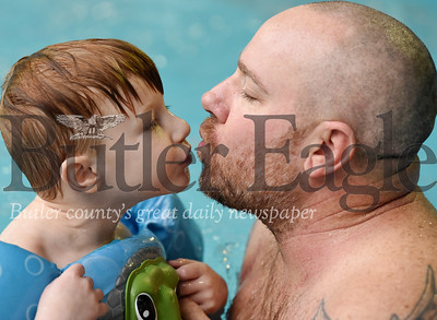 Harold Aughton/Butler Eagle: Presley, 4, gives his dad, Jason Rudge during the Autism Society swim event at Conley's Resort Monday, February 17, 2018.