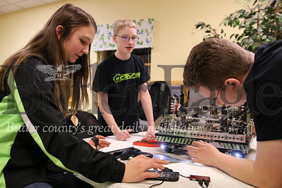 Lindsay Gourash, 15, Owen Anderson, 15, (center) and Nathan Hale, 15, troubleshoot an issue with their team robot Schrodinger. Seb Foltz/Butler Eagle