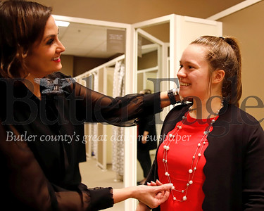 Outlet director of marketing and business development Michele Czerwinski adjust the colar and accessory necklace on Slippery Rock junior Kaya Weeks, one of the models for SRU's Dress for Success Fashion Show. Seb Foltz/Butler Eagle