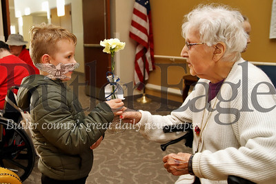 Joseph Hauser, 6, gives a flower to Rose Brough, a resident at Sunnyview Nursing and rehabilitation center. Students from Butler Catholic School delivered donated flowers leftover form Butler Catholic School's Purse Bash Fundraiser to residents at area senior care facilities Saturday. Students from Butler Catholic made cards and helped deliver the flowers following the previous night's fundraiser. Seb Foltz/Butler Eagle