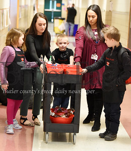 Harold Aughton/Butler Eagle: Kate Miller,left, learning support teacher, and Olivia Van der zee, emotional support teacher help students (left – right)  Izabella Gaston, Jeric Stahlman, and Wyatt Dlugolenski deliver Rocket fuel to teachers at the Slippery Rock Elmentary.