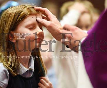 Harold Aughton/Butler Eagle: Maddie Krill, a 3rd grader at Butler Catholic, receives the distribution of ashes from Father Kevin Fazio during Mass Wednesday, February 26, 2020. Over three hundred students, teachers, staff and parents took part in the ceremony marking the beginning of the Lenten season.