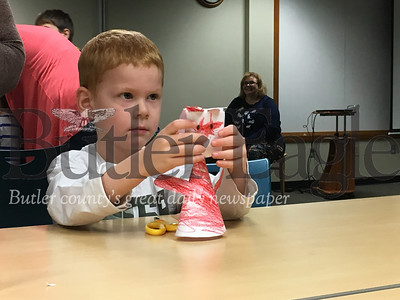 James Dickerman, 4 of Butler, sets the head on top of the paper cat he created as part of the Butler Public Library's Happy Mew Year event that took place on Jan. 2, 2019.