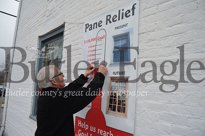 """Historic Harmony President Rodney Gasch updates the """"pane relief"""" fundraising chart for the window restoration project at the Wagner Haus. Pics by Alexandria Mansfield."""