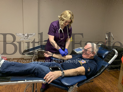 Elizabeth Langerud finishes off Jack Carney's 109th blood donation with a Band-Aid on Friday at a Vitalant blood drive at Elks Lodge in Cranberry Township.