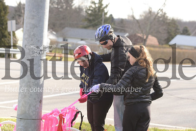"""Christina Teimouri, left, reads messages left on a """"ghost bike"""" for her son, Alek Teimouri."""