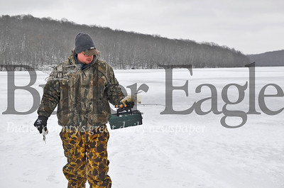 Bill McKeown, 38, carries tackle and caught fish between fishing holes on Lake Arthur. Tanner Cole/Butler Eagle