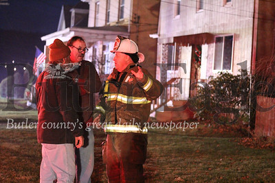 Dan Rowe, 59, center, along with his friend Bruce Fresh, 63, speak with Bruin Volunteer Fire Department Chief Eric Feicht, right, on a neighbors lawn while 12 fire crews work together to put out a fire that destroyed the home that Rowe's been renting for 20 years. The home caught fire on the evening of  January 13.Photo by Lauryn Halahurich/Butler Eagle
